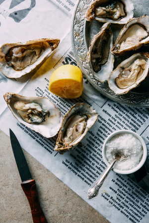 flat lay with oysters, lemon, salt and knife on newspaper on grey surface
