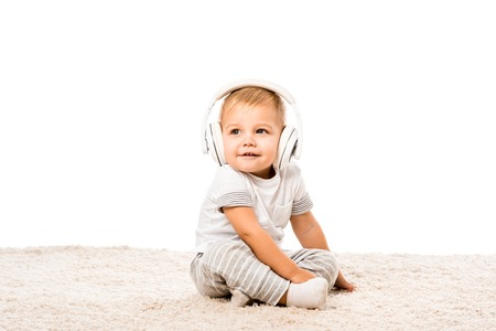 toddler boy sitting on carpet with headphones isolated on white