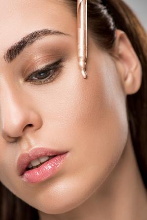 aantrekkelijk meisje markeerstift of bronzer met pipet aan te brengen