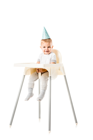 adorable toddler boy with blue party hat on head smiling and sitting in highchair isolated on white