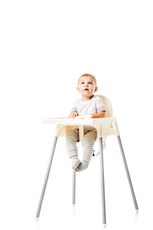 cute toddler sitting in highchair and looking up isolated on white