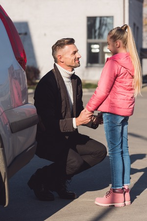 Dad holding hands of daughter near car Banque d'images - 112747348