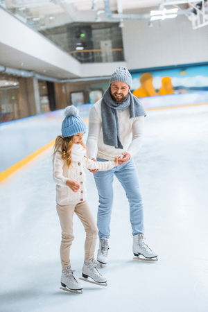 father and daughter in knitted sweaters skating on ice rink together