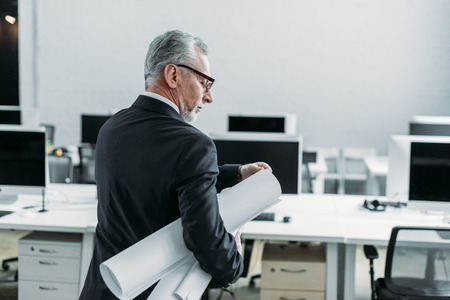 back view of senior businessman with blueprints in office