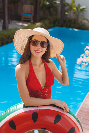 attractive young woman in swimsuit with inflatable ring at poolside