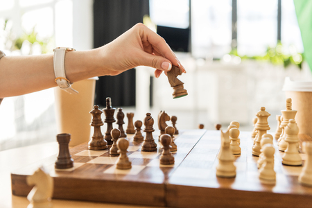 cropped shot of young woman playing chess