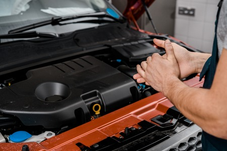 cropped shot of repairman standing at car with opened cowl at auto repair shop Stock Photo - 112749171