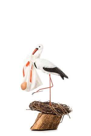 decorative stork holding baby nappy with doll and standing in wicker nest isolated on white Standard-Bild - 112749183