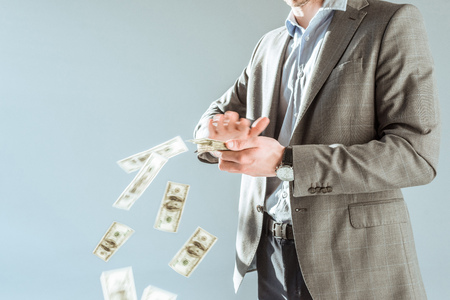 Close-up view businessman throwing money isolated on grey