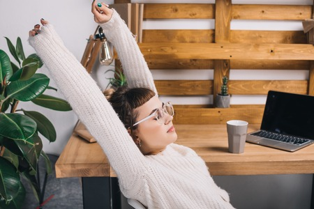 side view of girl stretching on chair in office Stock Photo