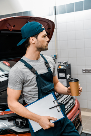 pensive mechanic with coffee to go and notepad leaning on car with opened cowl at mechanic shop