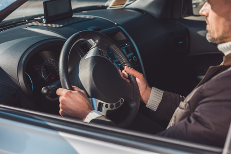 Man sitting and driving car in daytime