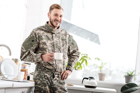 Soldado del ejército sonriente sosteniendo una taza de café en la cocina Foto de archivo