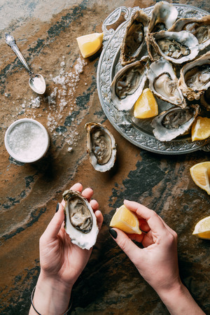 cropped shot of woman holding oyster and lemon piece in hand at grungy tabletop Stock Photo