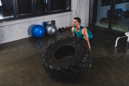 sportsman lifting tire during cross training in gym