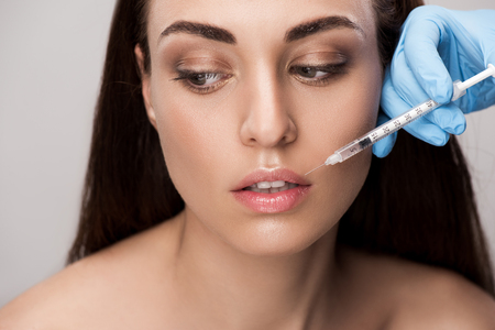 doctor making beauty injection into lips for attractive girl isolated on grey