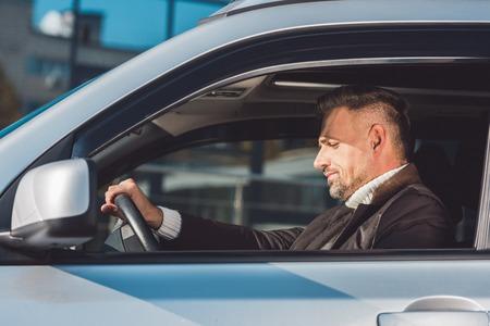 Handsome man sitting in car in daytime