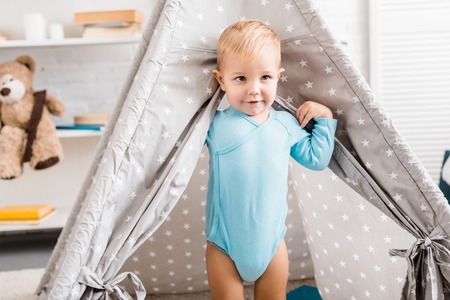 cute toddler boy in blue bodysuit standing in baby wigwam