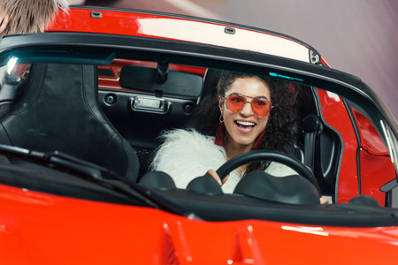 happy stylish young african american woman in fur coat driving luxury luxury car Stock Photo