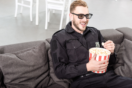 policeman in 3d glasses sitting on couch, eating popcorn and watching movie 写真素材