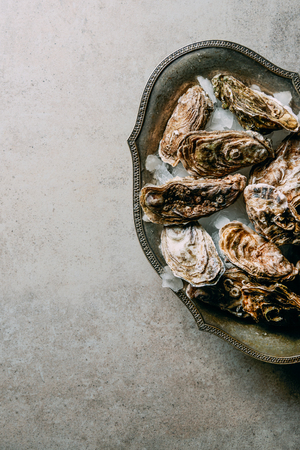 flat lay with oysters in metal bowl with ice on grey surface