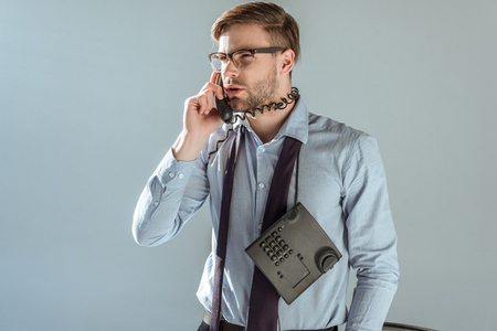 Young dissatisfied businessman talking on the phone isolated on grey