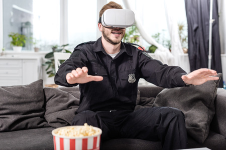 police officer with virtual reality headset on head sitting on couch and playing video game 写真素材 - 112757374