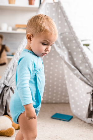 close up view of cute toddler boy in blue bodysuit standing near grey baby wigwam Stock Photo