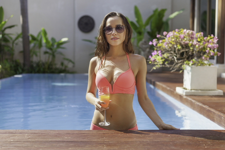 attractive young woman in bikini at poolside Stockfoto