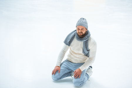 bearded man fell while skated on ice rink Stock Photo