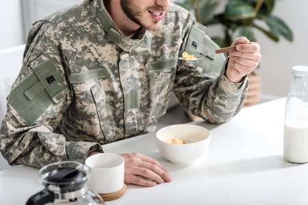 cropped view of man in camouflage uniform having breakfast in morning