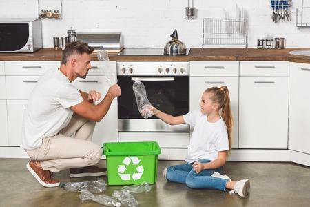 father and daughter sitting on floor at kitchen and putting empty plastic bottles in box with recycle sign