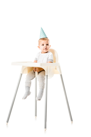 adorable toddler boy with blue party hat on head sitting in highchair isolated on white