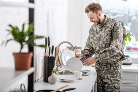army soldier cleaning dishes in kitchen