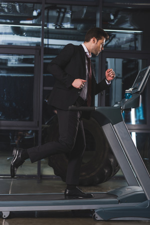 handsome businessman running on treadmill in gym