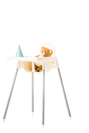 teddy bear sitting in highchair isolated on white Stock Photo - 112757551