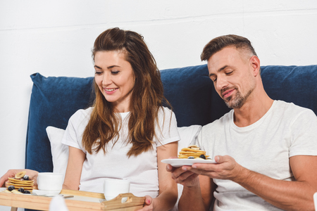 adult smiling couple eating pancakes in bed