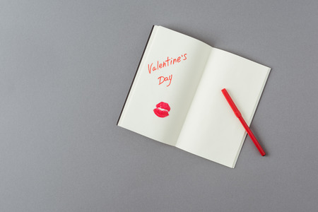 top view of open notebook with note and lips print on gray surface