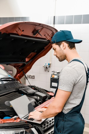 side view of auto mechanic working on laptop at automobile with opened car cowl at mechanic shop