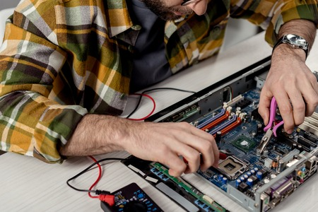 man using multimeter and tongs while fixing pc
