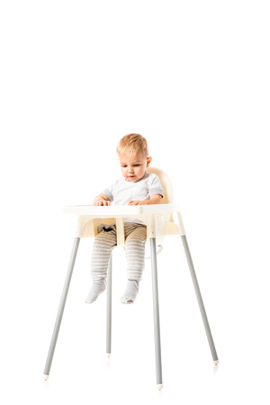 cute toddler sitting in highchair isolated on white