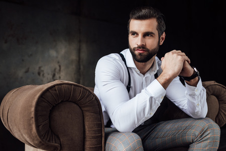 handsome bearded man thinking and sitting in armchair