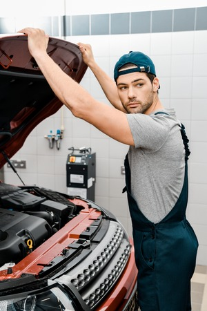 auto mechanic looking away examining car cowl at workshop