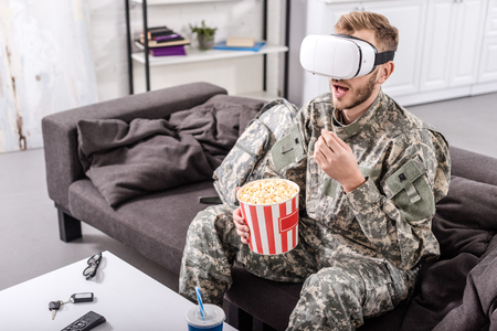 soldier wearing virtual reality headset, sitting on couch, watching movie and eating popcorn