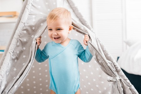 close up view of smiling toddler boy in blue bodysuit standing in baby wigwam