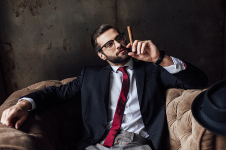 fashionable man sitting in armchair and holding cigar Zdjęcie Seryjne - 112757706