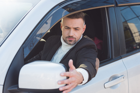 Handsome man looking in mirror and sitting in car Stock Photo