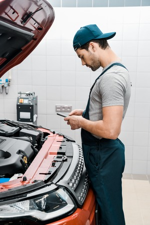 auto mechanic in uniform using smartphone at car with opened cowl at mechanic shop Stock Photo