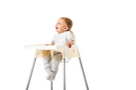 happy toddler boy smiling and sitting in highchair isolated on white