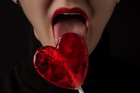 cropped image of woman licking heart shaped lollipop isolated on black Stok Fotoğraf